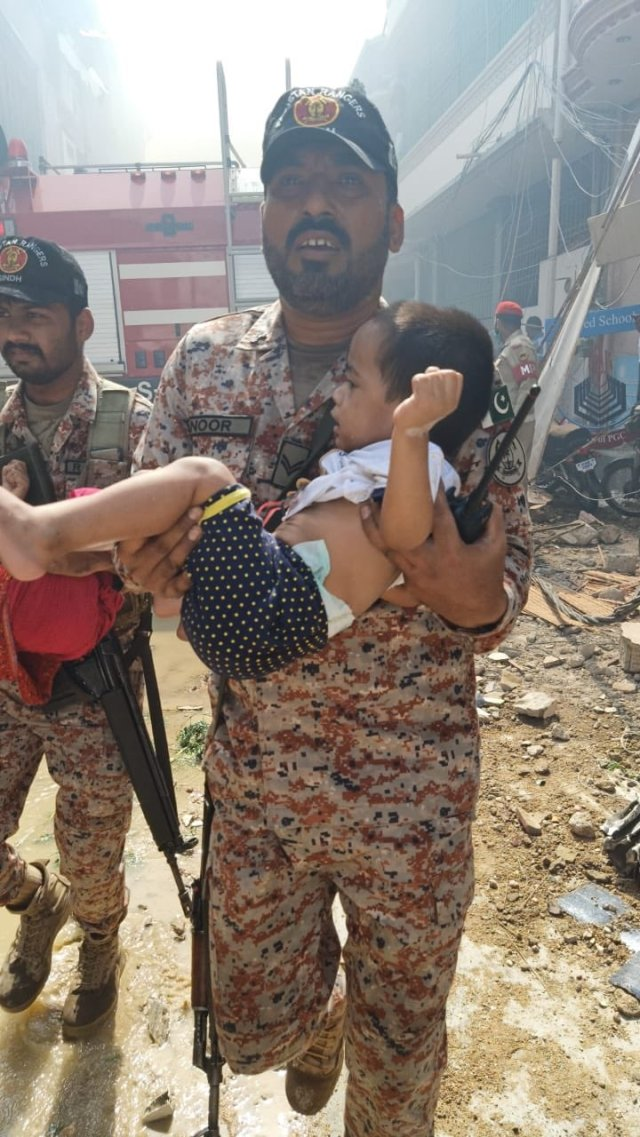 A child is carried away from the crash scene which left several houses destroyed