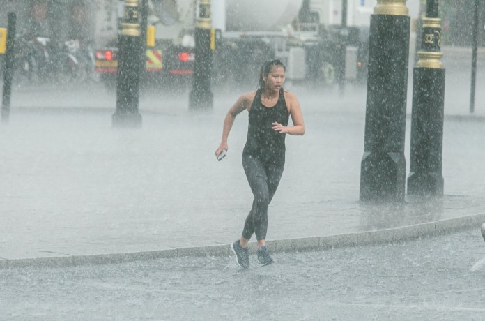 A jogger is caught in a heavy downpour in central London