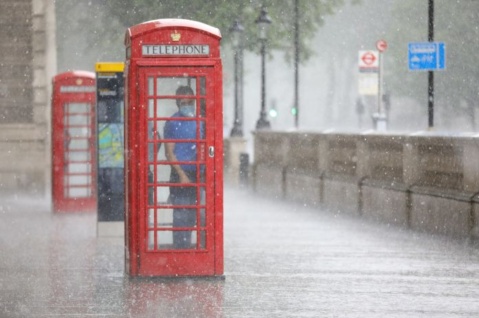Londoner takes refuge in telephone booth as storm hits capital