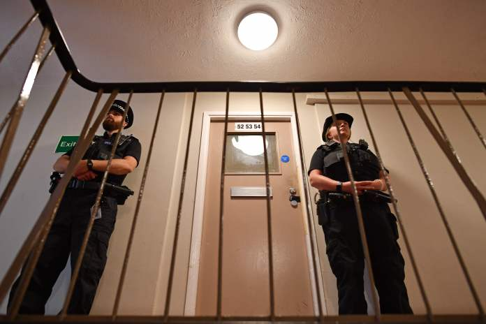 Police officers stand guard in a doorway inside a block of flats where the suspect is believed to have lived