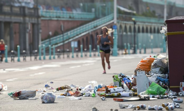 A runner passes piles of litter on the Brighton seafront this morning
