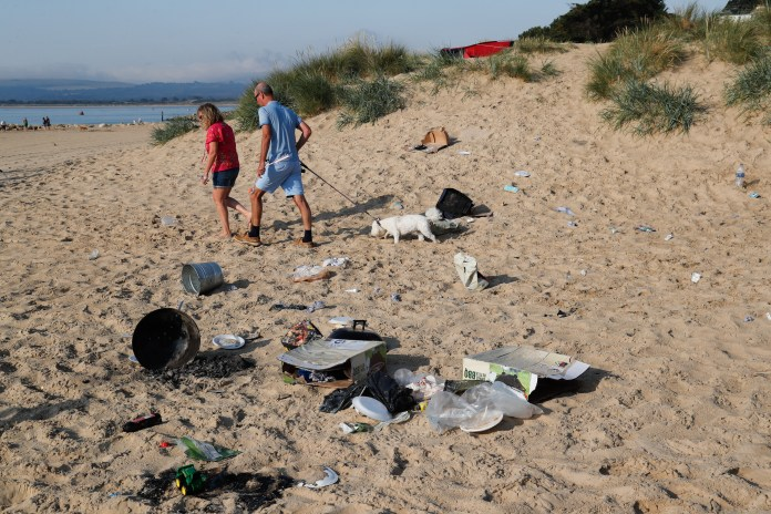 Couple walks dog in mess left at Sandbanks this morning
