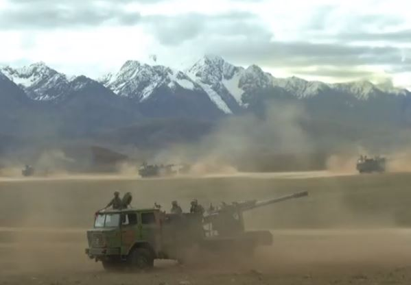 Chinese artillery opens fire with mountains in the background