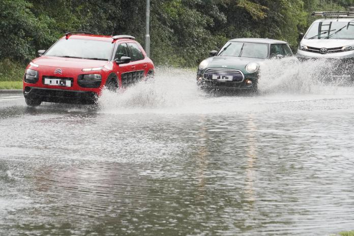 Cars cross flash floods as Essex roads are submerged after heavy rain at Ingatestone