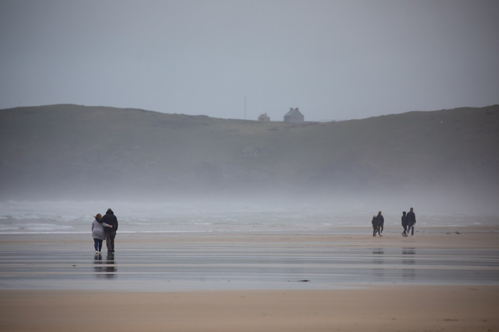 People braved the cold and windy conditions of Perranporth Beach in Cornwall on Saturday