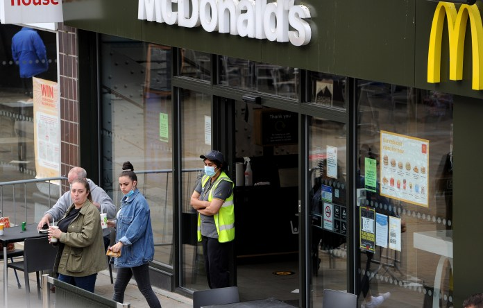 Staff stand outside a McDonald's in Blackburn as new mask rules take effect