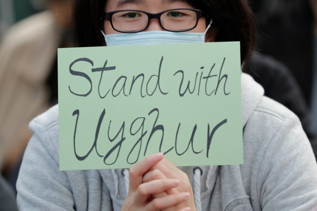 """A sign reads """"Stand with Uyghur"""" during a rally in Hong Kong"""