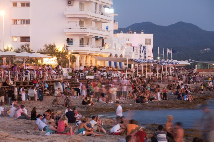 Cafe del Mar Beach full of people at dusk in Ibiza before lockdown