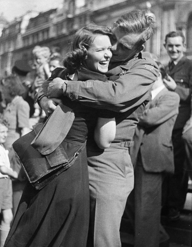 A male and female soldier embrace on hearing the news that Japan has surrendered in World War Two