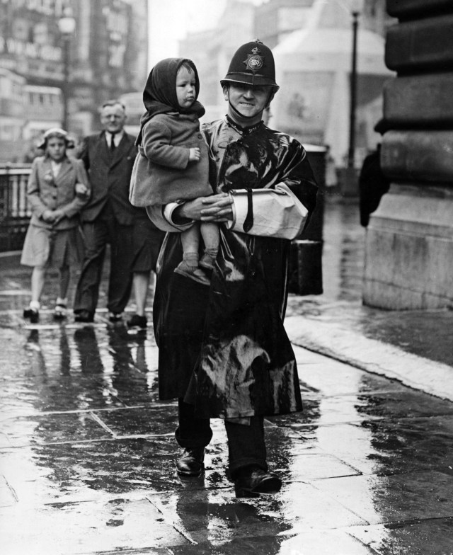 On VJ Day, a policeman carries a lost child in Trafalgar Square, London, August 15, 1945