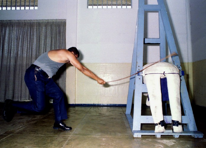 Prison officer demonstrates caning procedure at Changi Prison