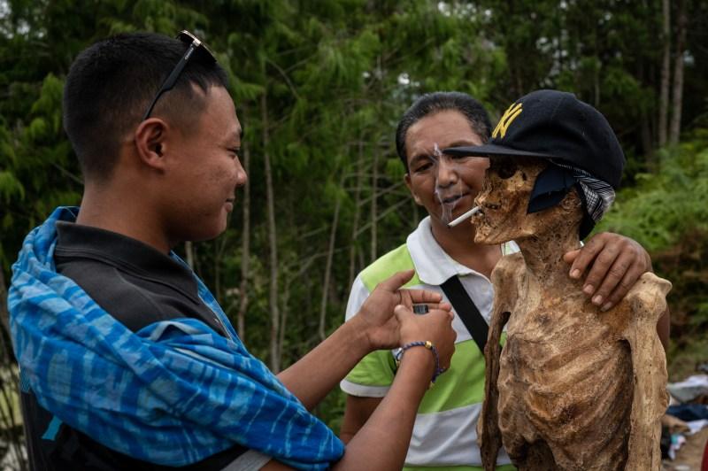 La tribu Toraja en Indonésie déterre leurs proches décédés, les habille et allume des cigarettes pour eux