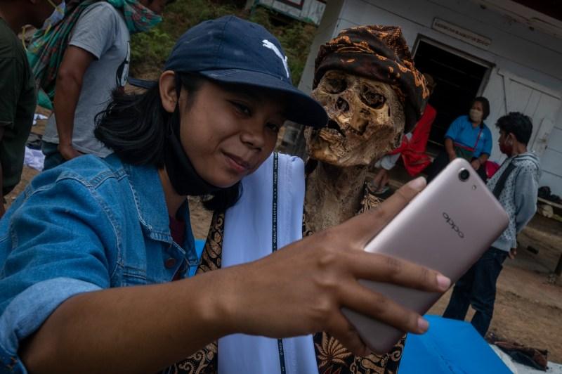 Un membre de la famille pose pour un selfie avec un cadavre