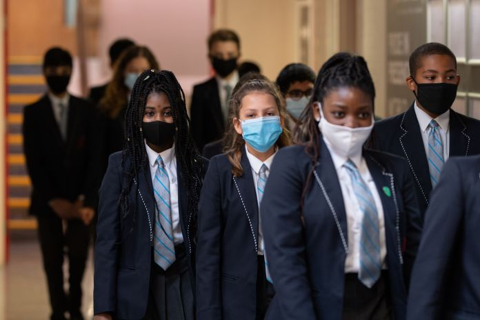 Year eight pupils wear face masks as they walk along a corridor of Moor End Academy in Huddersfield, West Yorks