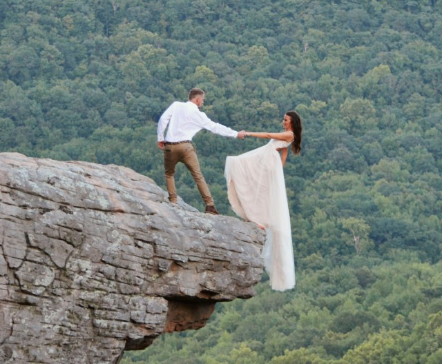 The couple posed right on the edge of the soaring cliff edge