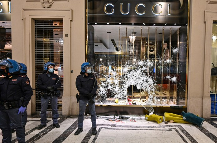 Police officers stand guard in front of destroyed Gucci store in Turin