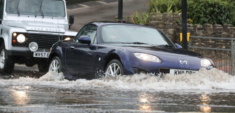 คนขับรถลุยน้ำท่วมที่ Branksome Chine ใน Poole, Dorset ในช่วง Storm Alex เมื่อวานนี้