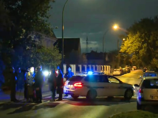 A camera crew films on as police cars guard the scene