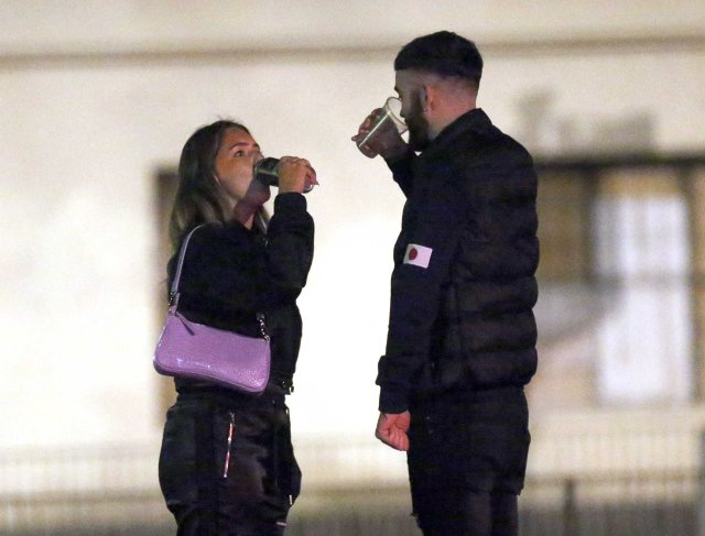 Friends sink their last pint on the streets of Leeds after closing time