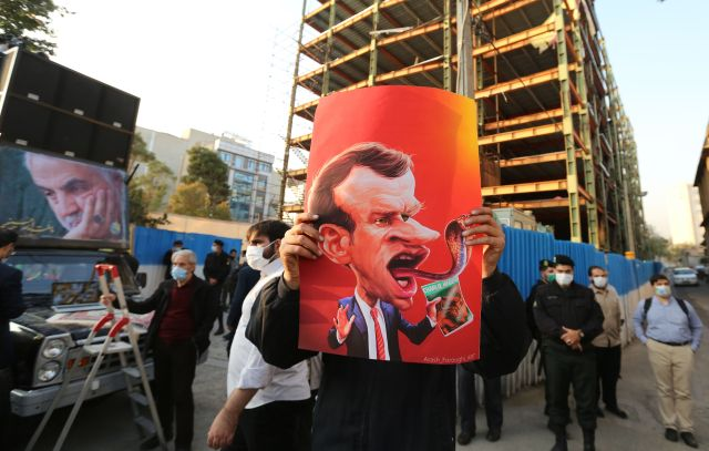 Iranian protester holds up a portrait of the French president with tongue in the shape of a snake