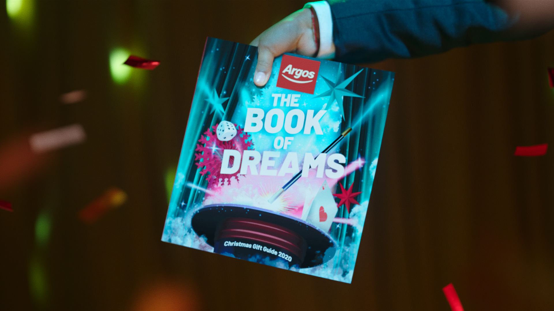 """The ad stars with the girls circling a magic trick set in the Argos Christmas gift guide, renamed """"The Book of Dreams"""""""