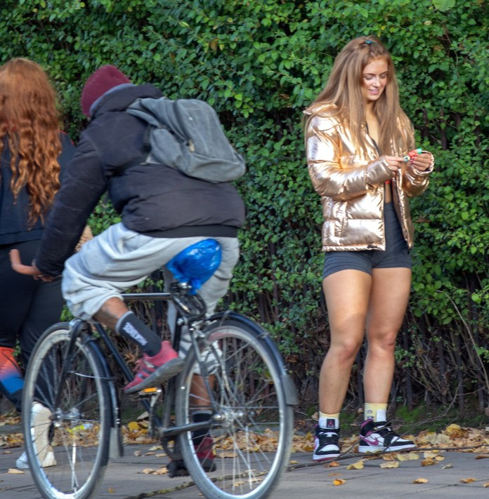 She was seen smiling as she looked at her phone on the sidewalk