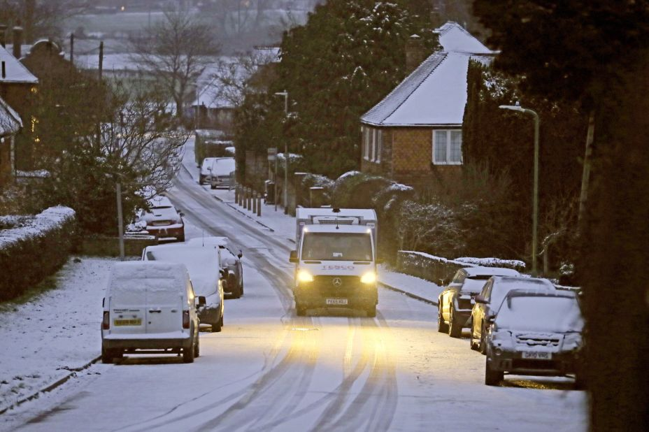 A Tesco delivery van makes its way along a road covered in snow near Ashford in Kent this morning