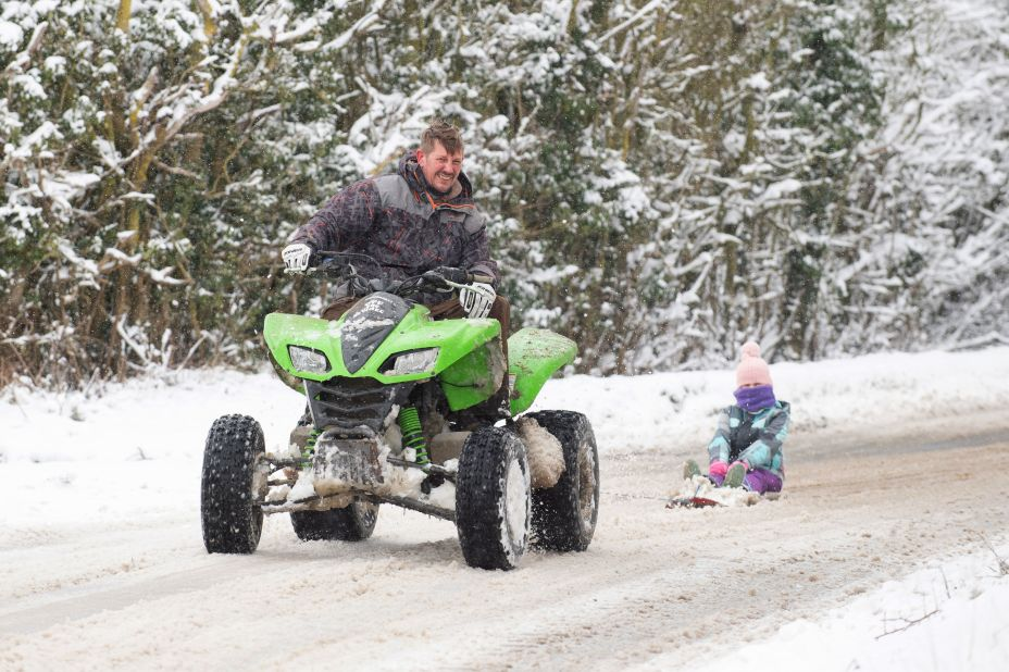 Richard Squirrell uses a quad bike to give his granddaughter Florence a ride in the snow in Wattisham, Suffolk