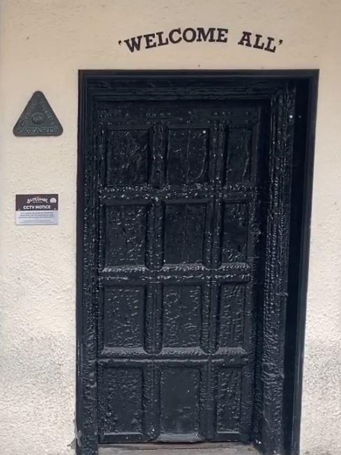 The door is covered in layers of black paint