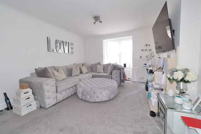 The living room has cute personal touches including a 'Love' sign