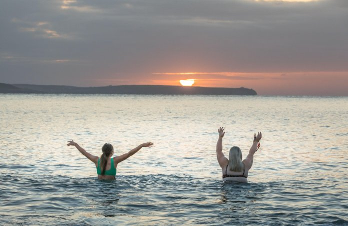 Swimmers enjoy a sunny start to the day in Cork, Ireland
