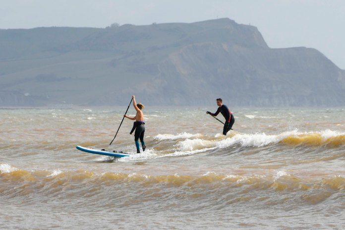 Paddle boarders on the sea catching a wave as they enjoy the sunshine at Lyme Regis in Dorset on a morning of warm sunny spells