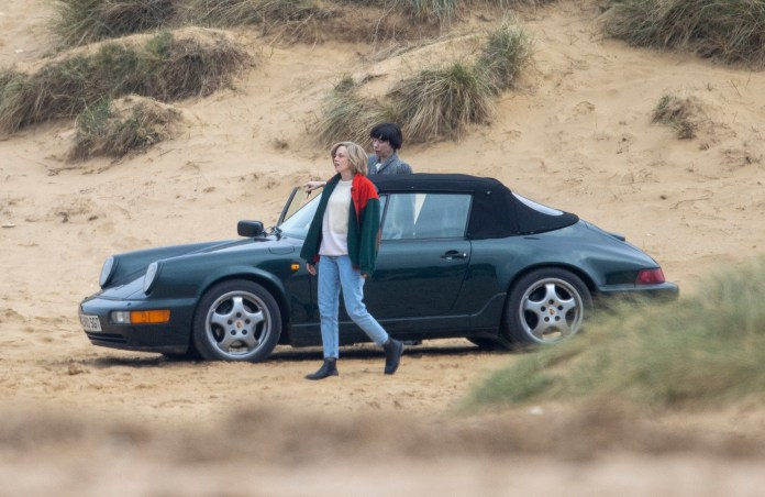 Kristen steps of out the car to take a stroll on the beach during filming