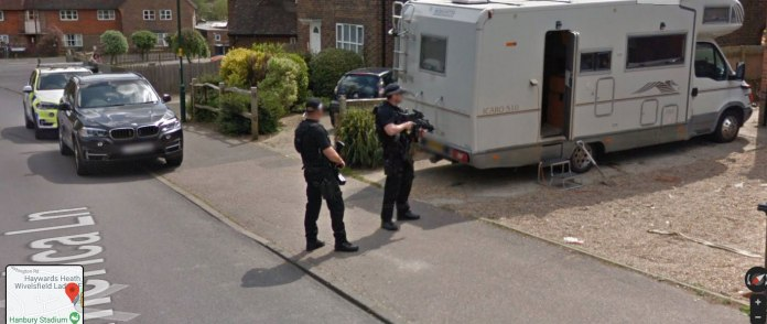Armed officers keep guard next to a caravan as police conduct enquiries