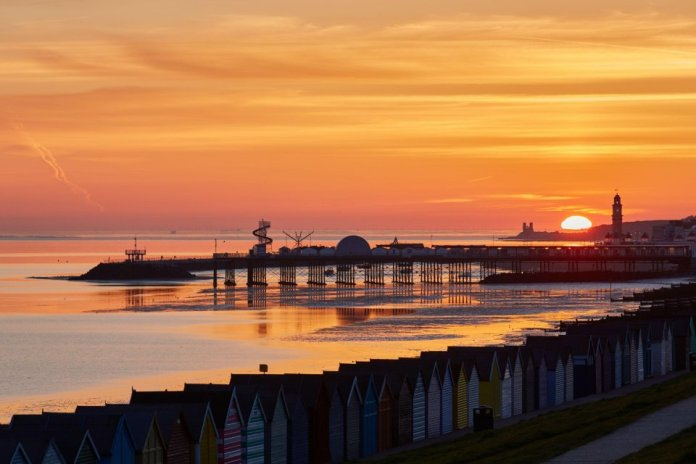 The sunrise created an orange glow between Reculver towers and the clock tower at Herne Bay