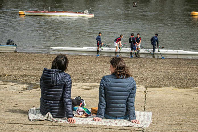 Brits have been warned to stay careful over Easter. Pictured: Two women sitting on the Thames riverside embankment in Putney, April 1