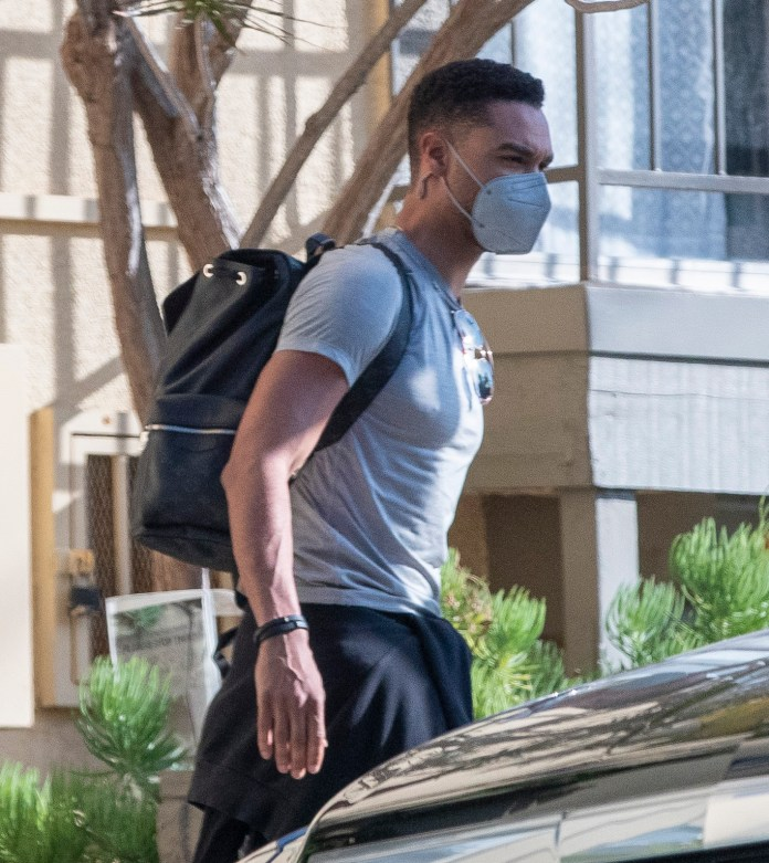 The actor wore a grey t-shirt which showed off his bulging muscles and carried a black Louis Vuitton rucksack