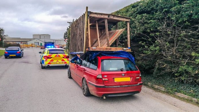This BMW driver was stopped by police for carrying a shed on his car