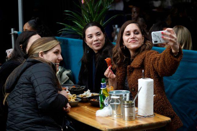 Friends take a selfie in Soho, central London