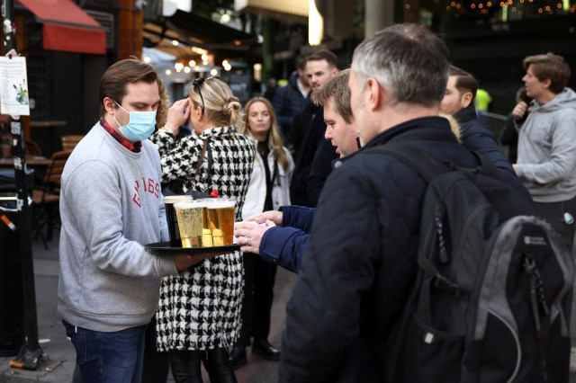 A bartender serves drinks to people on queue outside a bar in London