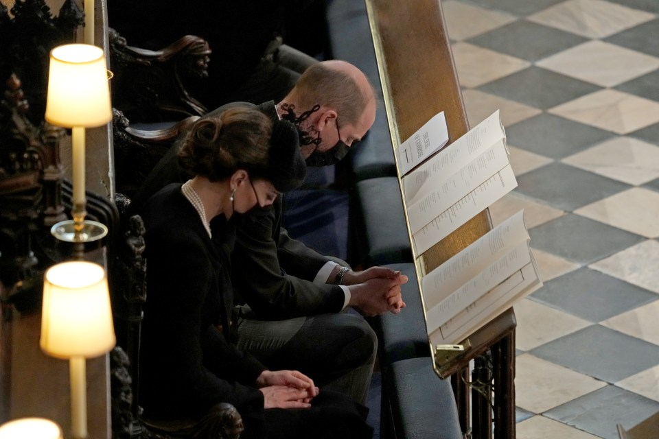 Prince William and Kate sitting with bowed heads and wearing masks