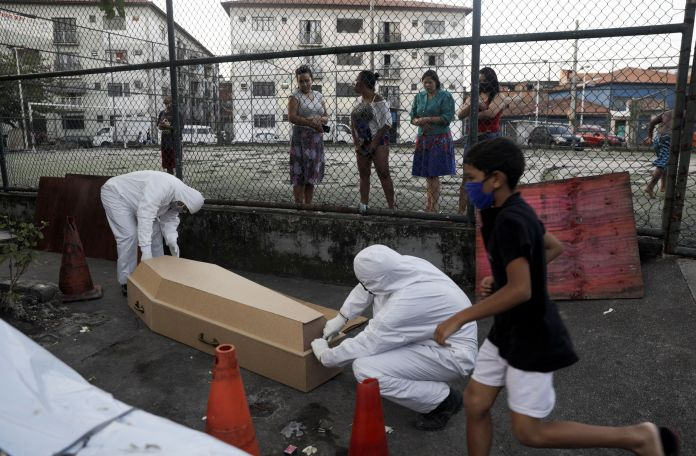 Workers of a funeral parlour, wearing protective clothing, place in a casket the body of Valnir Mendes da Silva, 62