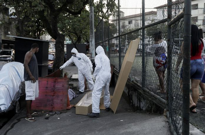 Workers of a funeral parlour, wearing protective clothing, remove the body of Valnir Mendes da Silva, 62, that was laying on a sidewalk of Arara community