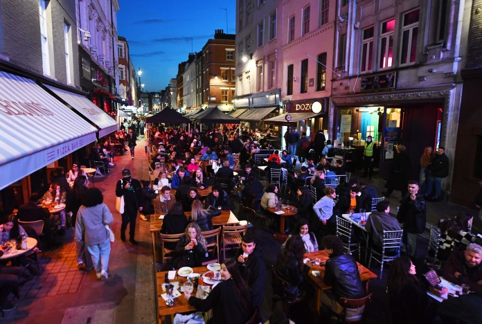 Partygoers have a drink on Old Compton Street in London's Soho