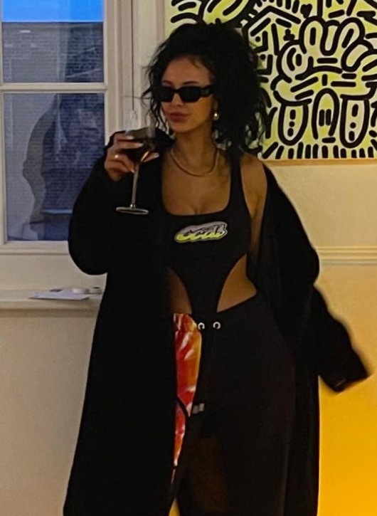 Maya Jama opted for all out drama with this high-cut body, tracksuit and maxi coat combo
