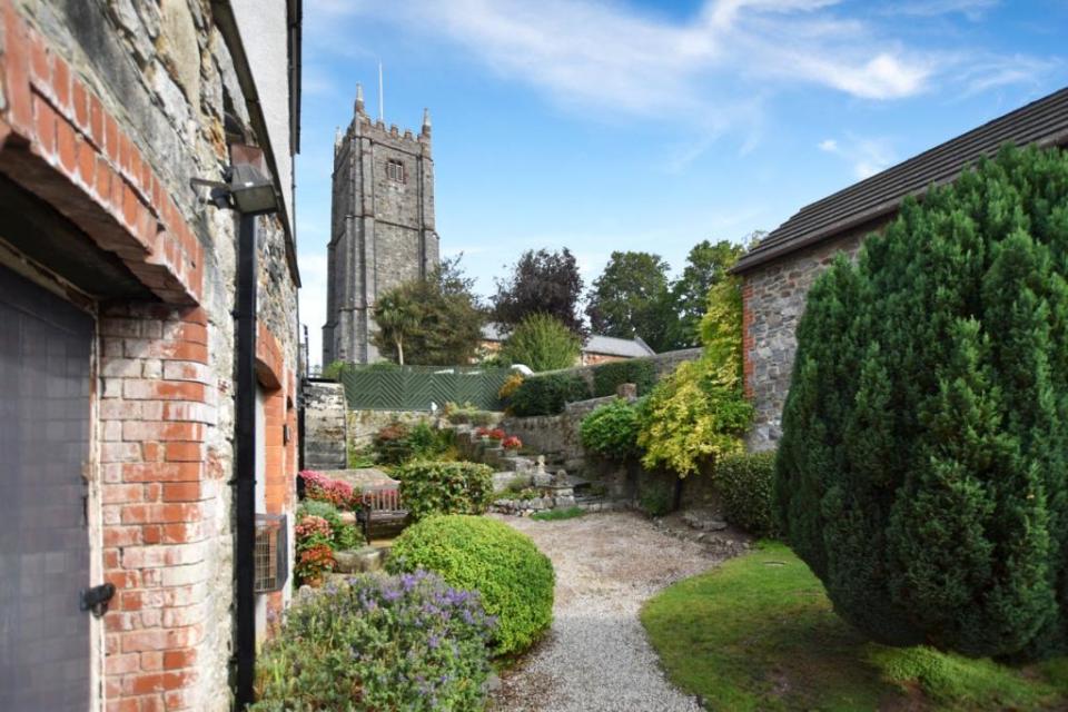 It is located next to a church in a quiet Devon village
