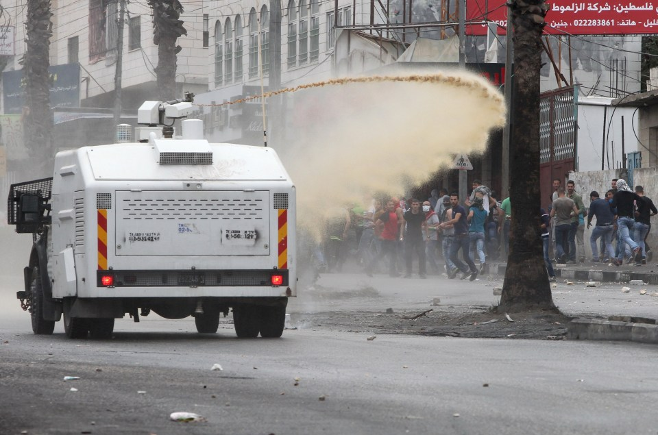 Israeli security forces spray foul-smelling water known as 'skunk' towards Palestinian stone throwers during clashes