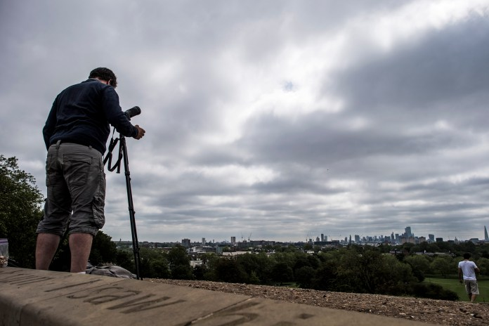 People in London trying to watch the eclipse through a cloud