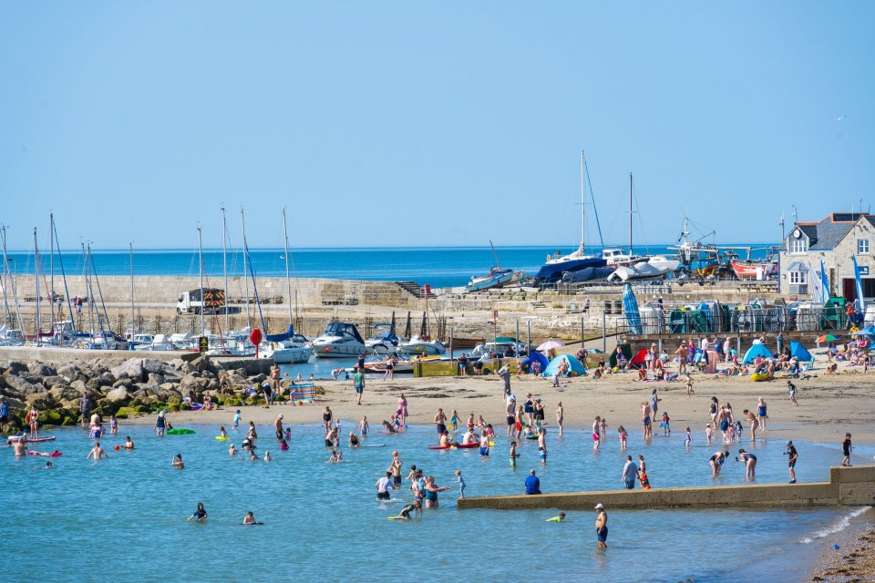 Visitors to Lyme Regis in west Dorset wade into the sea