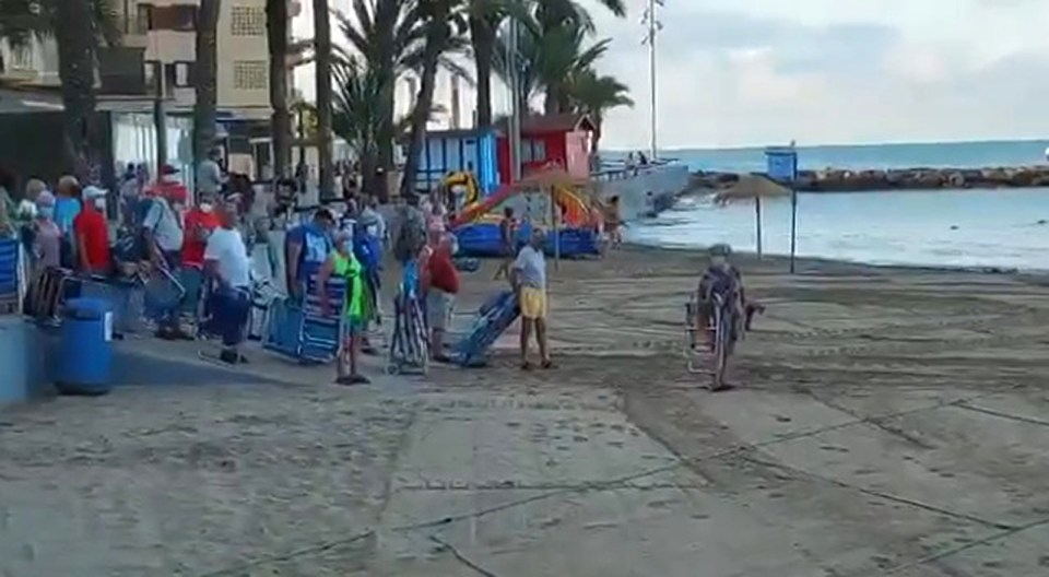Beachgoers can be seen waiting from 6am for the lifeguard to give the signal